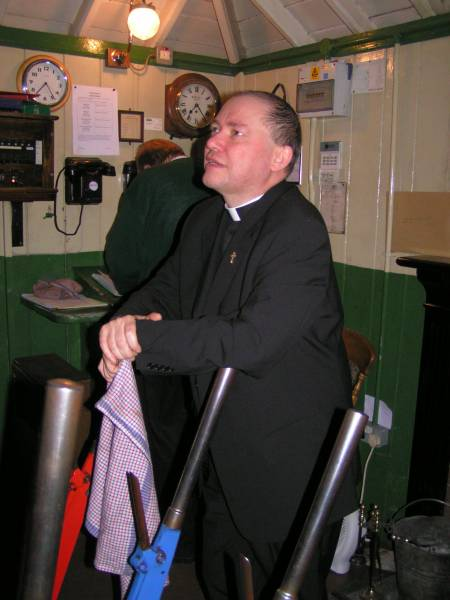Fr Michael Gill SSC, Rector of Cranford, in the signal box at Alresford on the Mid Hants Railway